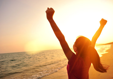 155395_cheering-woman-open-arms-to-sunset-at-seaside-000039083258_large