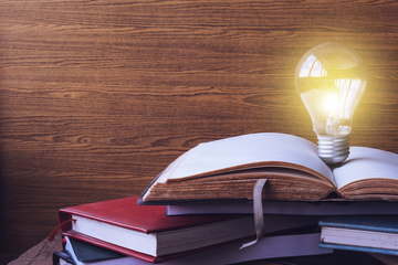 272241_open-book-with-light-bulb-and-hardback-books-on-wood-wall-background