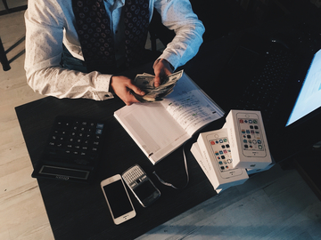 490192_canva - person counting money with smartphones in front on desk