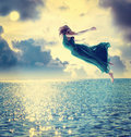 52049_beautiful-girl-jumping-night-sky-blue-over-ocean-48556079